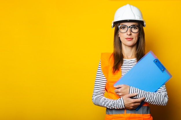 Mulher jovem de colete e capacete segurando uma prancheta amarela