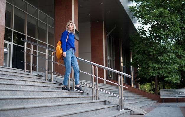 Mulher jovem de corpo inteiro descendo degraus após as aulas da universidade