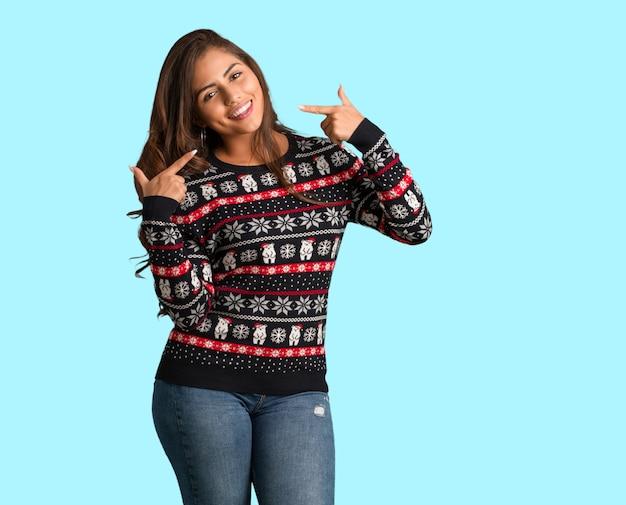 Mulher jovem de corpo inteiro vestindo uma camisa de natal sorri, apontando a boca
