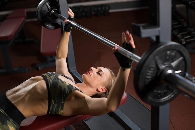 Mulher jovem de esportes fazendo exercícios com peso no banco no ginásio. bar bench press.