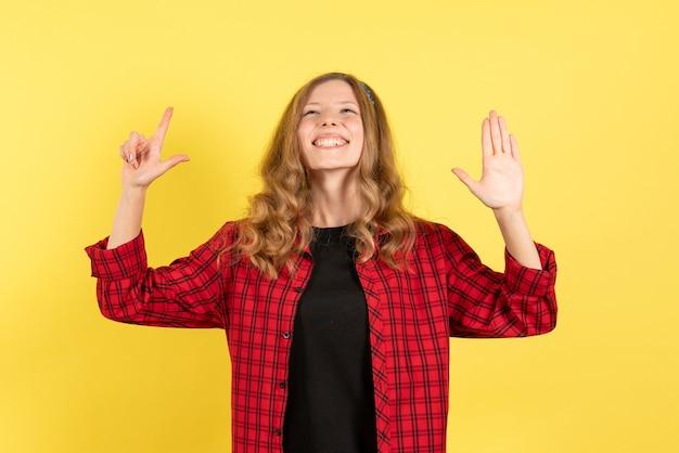 Mulher jovem de frente, camisa quadriculada vermelha, sentindo-se feliz com fundo amarelo mulher emoção humana modelo moda garota