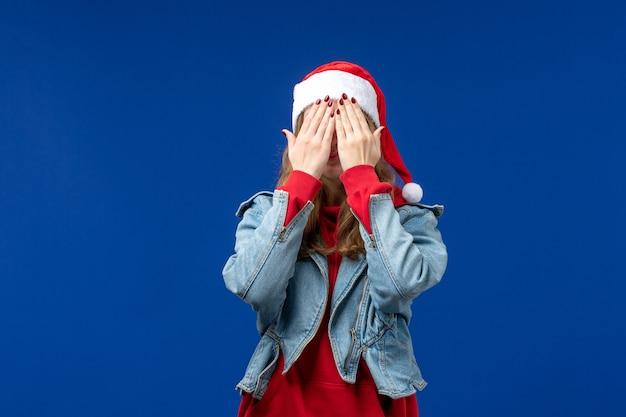 Mulher jovem de frente, cobrindo o rosto em fundo azul, cor de emoção de natal
