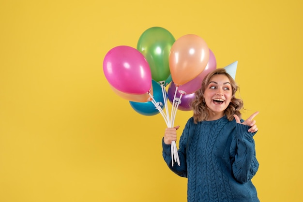 Mulher jovem de frente com balões coloridos