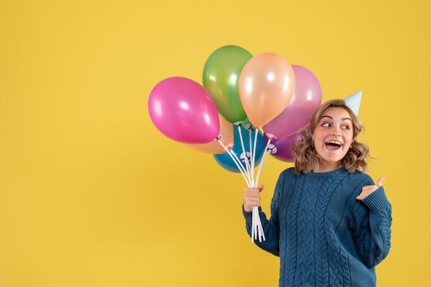 Mulher jovem de frente com balões coloridos Foto gratuita