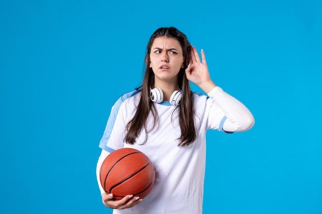 Mulher jovem de frente com basquete na parede azul
