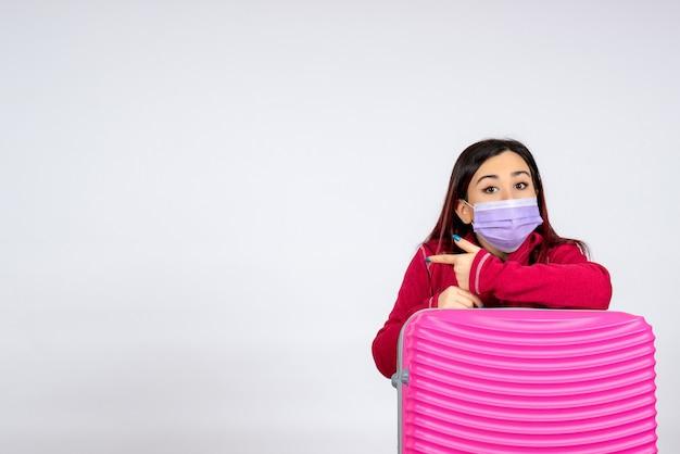 Mulher jovem de frente com bolsa rosa na máscara na parede branca vírus mulher férias covid cor pandemia viagem