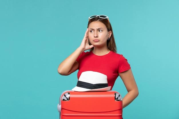 Mulher jovem de frente com bolsa vermelha e chapéu no espaço azul