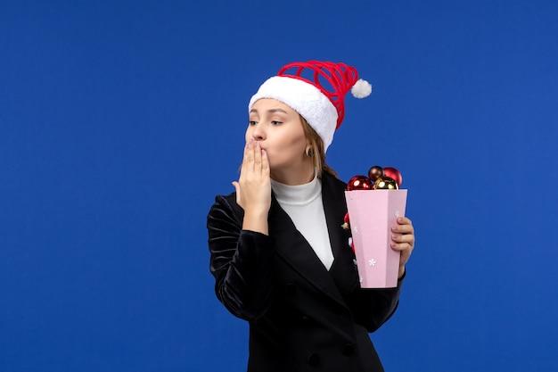 Mulher jovem de frente com brinquedos de árvore na cor das emoções do feriado de ano novo na parede azul