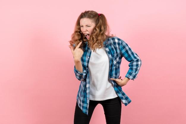 Mulher jovem de frente com camisa quadriculada azul, tendo problemas respiratórios na parede rosa, juventude, emoção, meninas, criança, modelo, moda