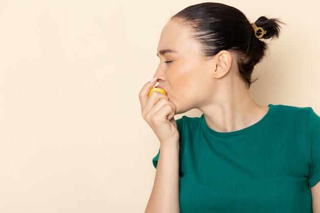 Mulher jovem de frente com camisa verde escura e jeans azul, mordendo limão azedo em bege