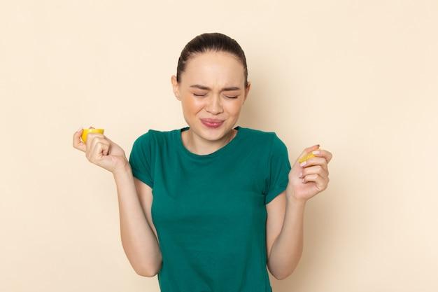 Mulher jovem de frente com camisa verde escura e jeans azul, mordendo limão em bege