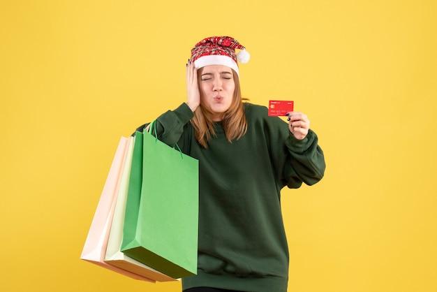 Mulher jovem de frente com cartão de banco e pacotes de compras
