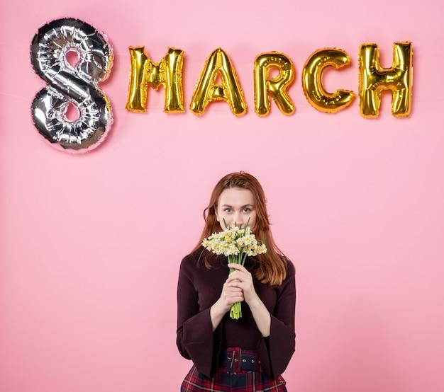 Mulher jovem de frente com flores nas mãos e decoração de marcha em fundo rosa festa dia das mulheres março casamento paixão igualdade presente