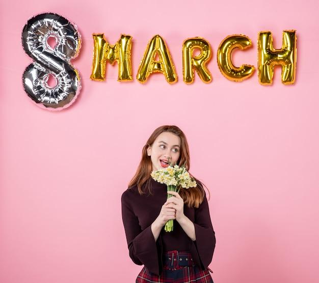 Mulher jovem de frente com flores nas mãos e decoração de marcha em fundo rosa festa dia das mulheres março casamento paixão igualdade presentes sensuais