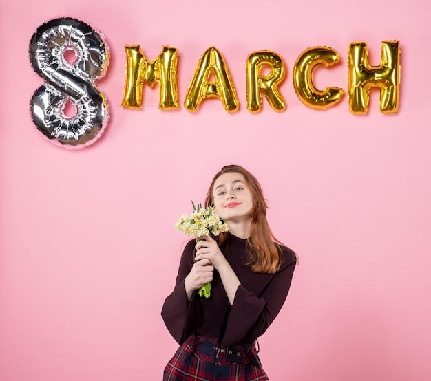 Mulher jovem de frente com flores nas mãos e decoração de marcha em fundo rosa presente dia das mulheres marcha paixão festa igualdade sensual