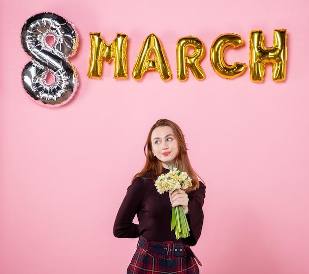Mulher jovem de frente com flores nas mãos e decoração de marcha no fundo rosa festa dia das mulheres marcha paixão igualdade presente sensual