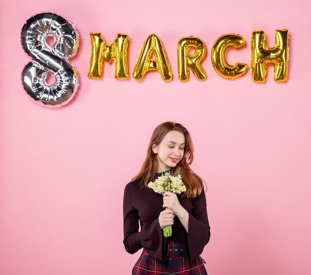 Mulher jovem de frente com flores nas mãos e decoração de marcha no fundo rosa festa dia das mulheres março casamento paixão sensual apresenta igualdade