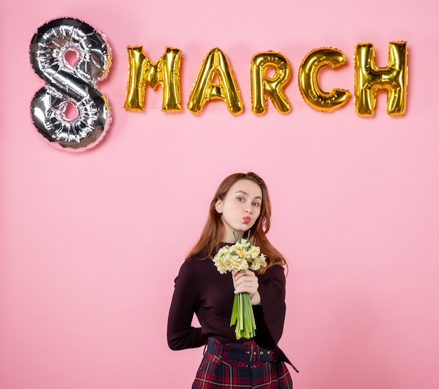 Mulher jovem de frente com flores nas mãos e decoração de marcha no fundo rosa festa dia das mulheres março casamento paixão sensual presente igualdade