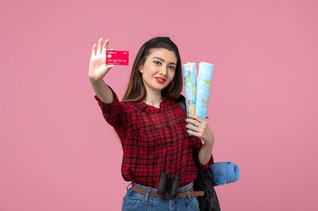 Mulher jovem de frente com mapas e cartão do banco na cor humana da mulher de fundo rosa