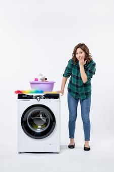 Mulher jovem de frente com máquina de lavar e shampoos na parede branca