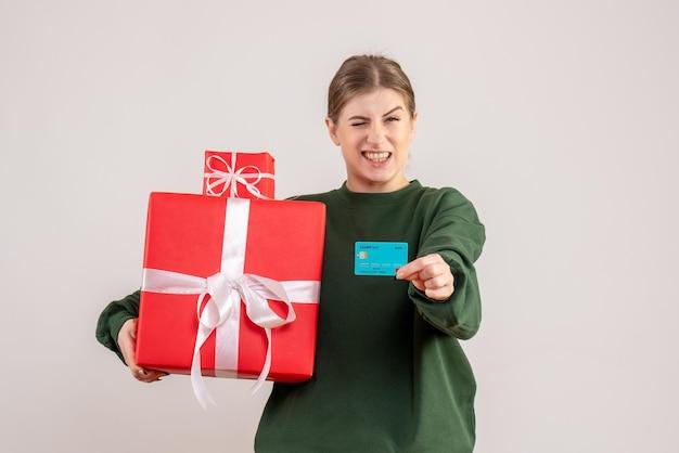 Mulher jovem de frente com presentes de natal e cartão do banco