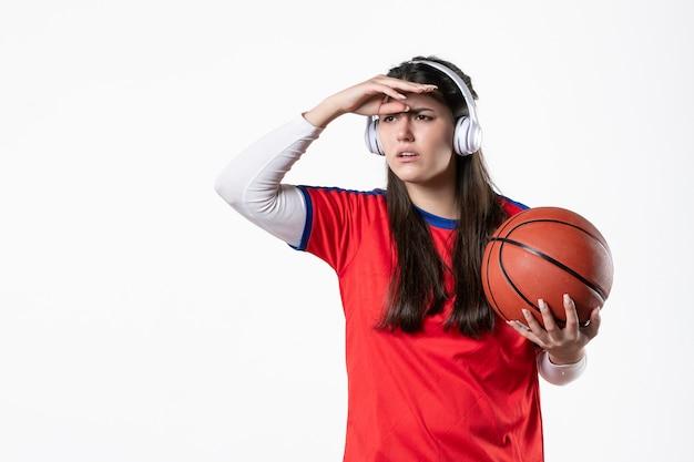 Mulher jovem de frente com roupas esportivas e parede branca de basquete