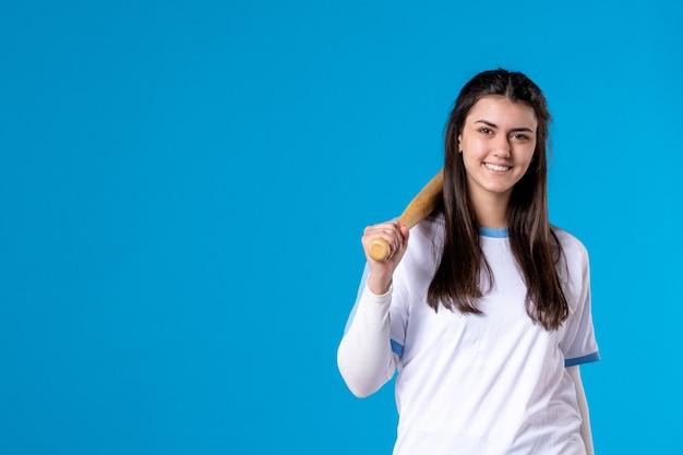 Mulher jovem de frente com taco de beisebol na parede azul