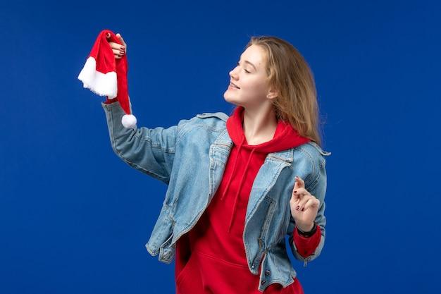 Mulher jovem de frente com tampa vermelha na mesa azul feriado natal ano novo