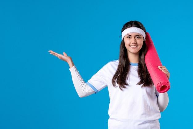 Mulher jovem de frente com tapete para exercícios na parede azul
