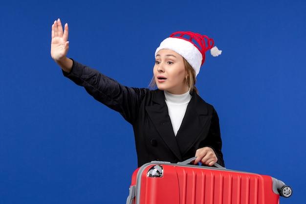 Mulher jovem de frente com uma grande bolsa vermelha na parede azul, ano novo, férias, férias, cor