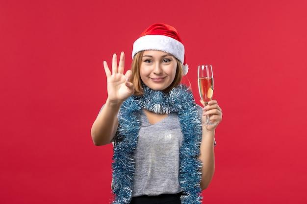 Mulher jovem, de frente, contando, mostrando o número na cor vermelha, feriado de natal