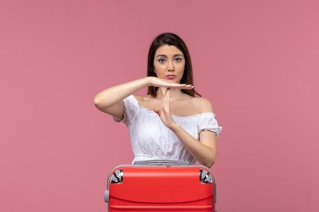 Mulher jovem de frente, de férias, mostrando o sinal de ti no fundo rosa no exterior