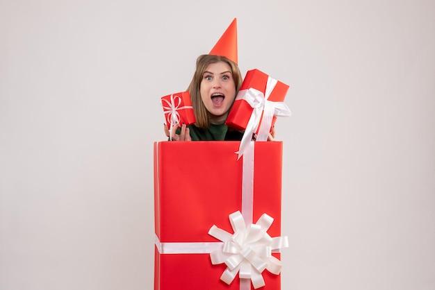 Mulher jovem de frente dentro de uma caixa vermelha com presentes