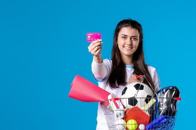 Mulher jovem de frente depois de fazer compras esportivas com cartão de crédito na parede azul