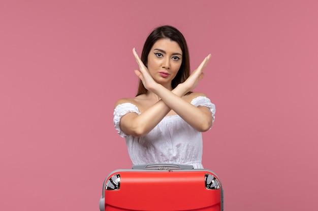 Mulher jovem de frente em férias mostrando sinal de proibição em fundo rosa no exterior viagem marítima viagem viagem viagem viagem