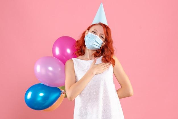 Mulher jovem de frente, escondendo balões coloridos atrás das costas com máscara estéril no fundo rosa, festa covid - natal cor de ano novo