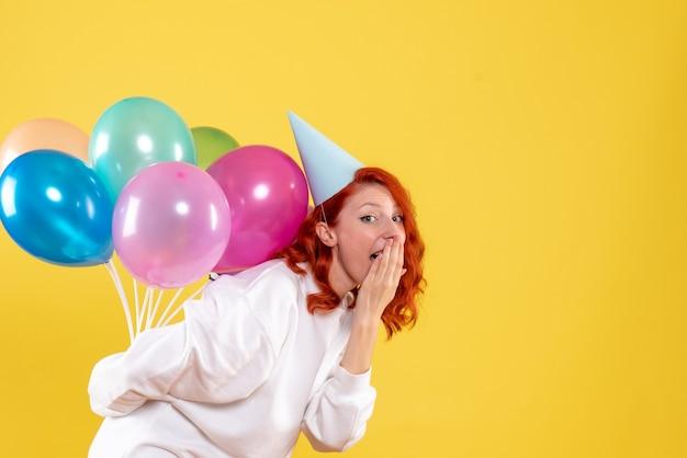 Mulher jovem de frente, escondendo balões coloridos atrás das costas, festa de ano novo, emoção, mulher natal