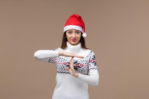 Mulher jovem de frente mostrando a letra t no fundo marrom emoção feriado de natal