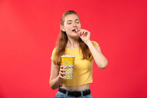 Mulher jovem de frente no cinema segurando pipoca e comendo na parede vermelha filmes teatro cinema filme garota