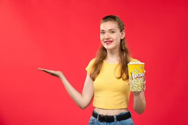 Mulher jovem de frente no cinema segurando pipoca e sorrindo na parede vermelha.