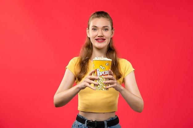 Mulher jovem de frente no cinema segurando um pacote de pipoca e sorrindo na parede vermelha filmes teatro cinema lanche feminino divertido filme