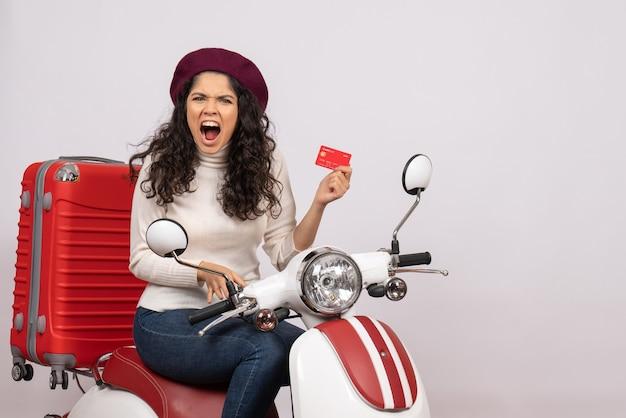 Mulher jovem de frente para a bicicleta segurando um cartão do banco vermelho no fundo branco cidade cor estrada veículo motocicleta velocidade férias dinheiro