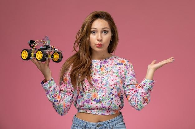 Mulher jovem de frente para a camisa com design flor e calça jeans, pensando e segurando o carro de brinquedo no fundo rosa