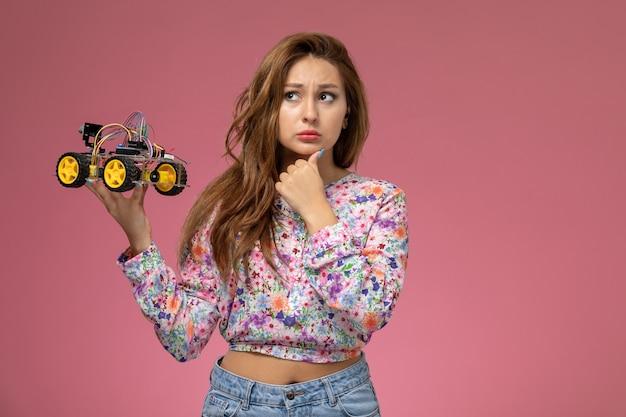 Mulher jovem de frente para a camisa com design flor e calça jeans segurando o carrinho de brinquedo com expressão pensativa no fundo rosa