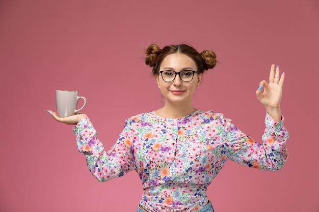 Mulher jovem de frente para a camisa com design flor e calça jeans segurando o copo no fundo rosa