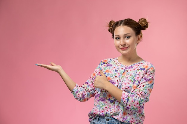 Mulher jovem de frente para a camisa com design floral e calça jeans, posando com um leve sorriso no fundo claro