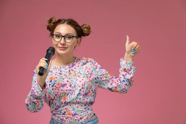 Mulher jovem de frente para a camisa com design floral e calça jeans segurando o microfone, tentando cantar na luz de fundo