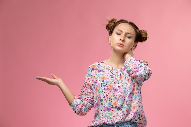 Mulher jovem de frente para a camisa com design floral e jeans azul, doendo no pescoço devido ao fundo claro