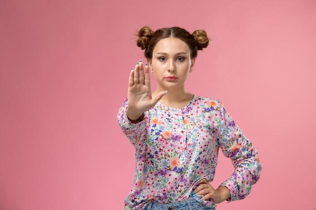 Mulher jovem de frente para a camisa com design floral e jeans azul mostrando o sinal de pare no fundo rosa