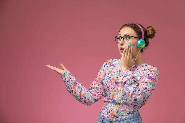 Mulher jovem de frente para a camisa com design floral e jeans azul, ouvindo música com fones de ouvido no fundo rosa, pose feminina